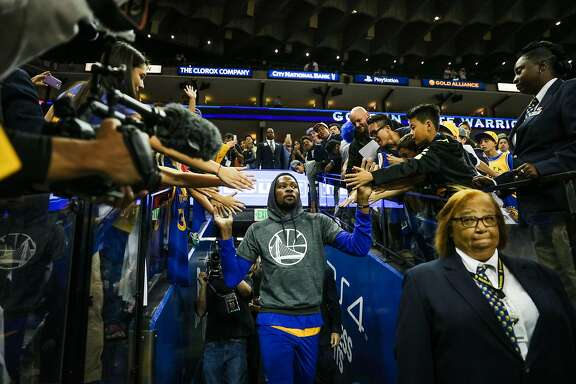 Warriors forward Kevin Durant, #35, gives high fives to fans as he heads to a warm up, ahead of a game between the Warriors vs. the Spurs, at Oracle Arena, in Oakland, California, on Tuesday, Oct. 25, 2016.