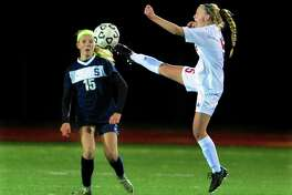 Fairfield Warde's Lauren Tangney leaps in to intercept the ball away from Staples Olivia Ronca during girls soccer action in Fairfield, Conn., on Tuesday Oct. 25, 2016.