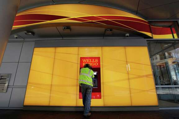 A customer uses an ATM outside a Wells Fargo branch in Charlotte, N.C.
