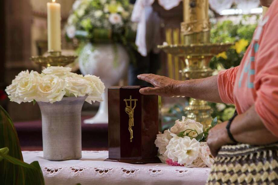 Parishioners and friends show their respect to the urn with the ashes of Catholic priest Jose Alfredo Lopez in the Santisima Trinidad church in the Janamuato community, Michocan state, Mexico on September 26, 2016. The Vatican has issued guidelines to Catholics stating that cremains are not to be scattered, divvied up nor kept in a urn on the mantlepiece but rather stored in a sacred, church-approved place. Photo: Enrique Castro / AFP /Getty Images / AFP or licensors