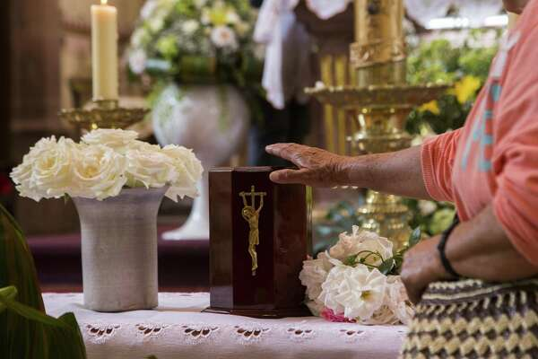 Parishioners and friends show their respect to the urn with the ashes of Catholic priest Jose Alfredo Lopez in the Santisima Trinidad church in the Janamuato community, Michocan state, Mexico on September 26, 2016. The Vatican has issued guidelines to Catholics stating that cremains are not to be scattered, divvied up nor kept in a urn on the mantlepiece but rather stored in a sacred, church-approved place.
