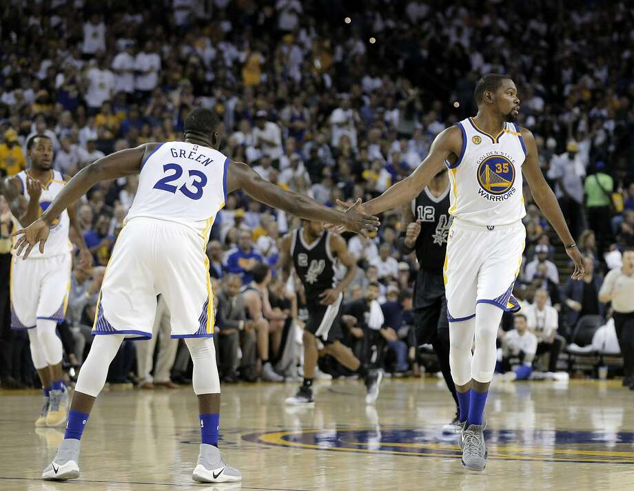 Draymond Green (23) high fives Kevin Durant (35) after Durant dunked in the first half as the Golden State Warriors played the San Antonio Spurs in their season opener at Oracle Arena in Oakland, Calif., on Tuesday, October 25, 2016. Photo: Carlos Avila Gonzalez, The Chronicle