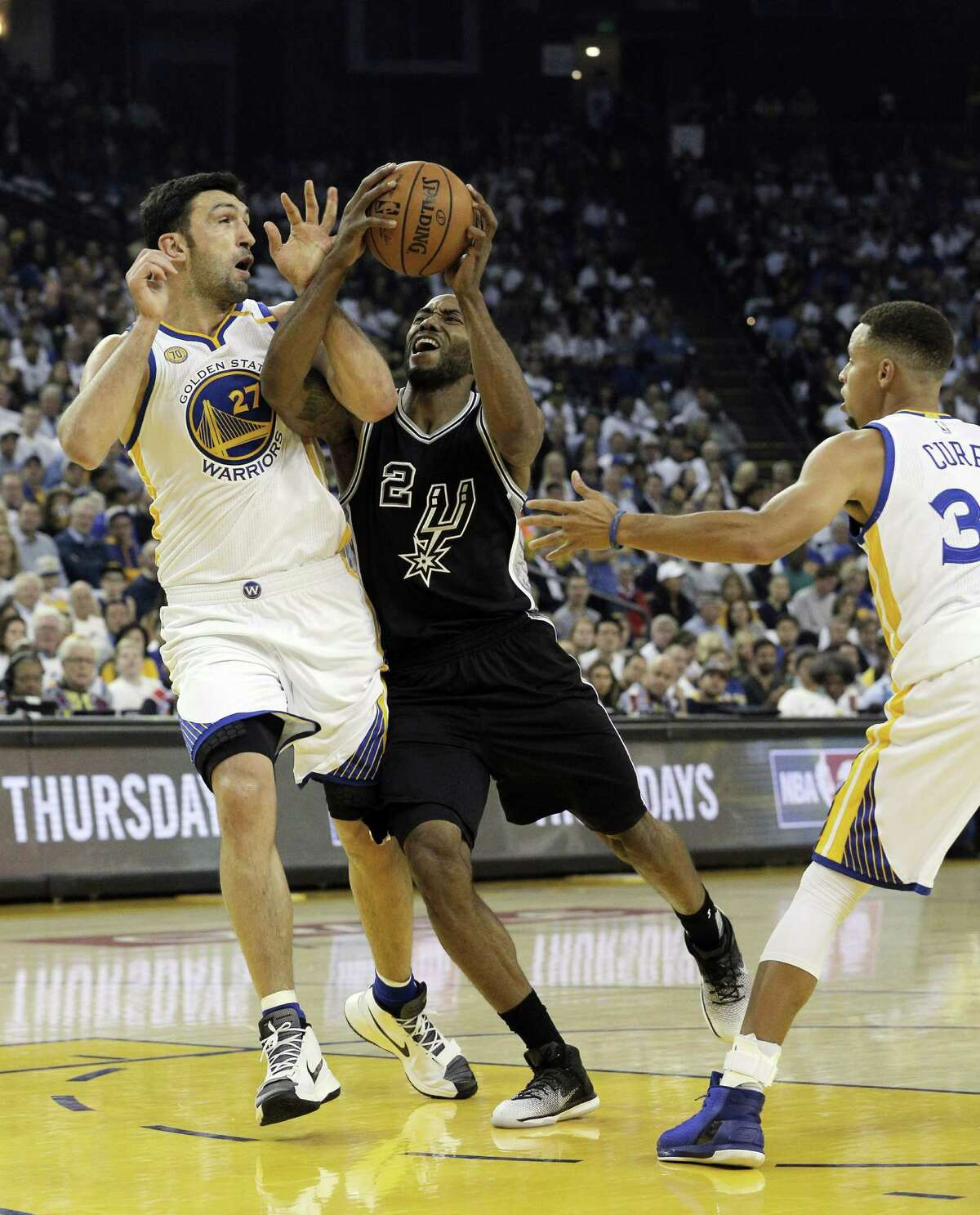 Kawhi Leonard (2) drives into ZaZa Pachulia (27) in the first half as the Golden State Warriors played the San Antonio Spurs in their season opener at Oracle Arena in Oakland, Calif., on Tuesday, October 25, 2016.