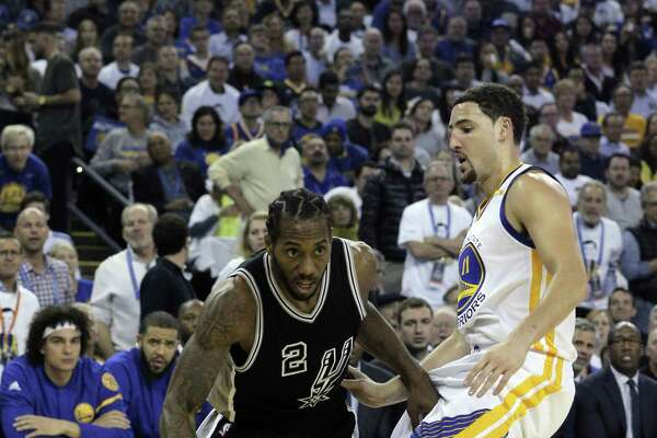 Klay Thompson (11) tries to keep Kawhi Leonard (2) from reaching the basket in the first half as the Golden State Warriors played the San Antonio Spurs in their season opener at Oracle Arena in Oakland, Calif., on Tuesday, October 25, 2016.