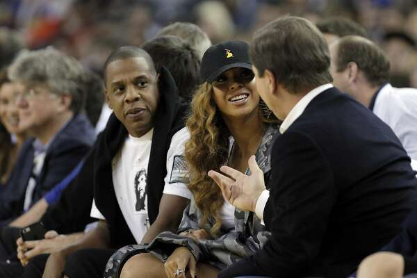 Jay-Z and Beyonce chat with Warriors owner Joe Lacob, right, in the first half as the Golden State Warriors played the San Antonio Spurs in their season opener at Oracle Arena in Oakland, Calif., on Tuesday, October 25, 2016.