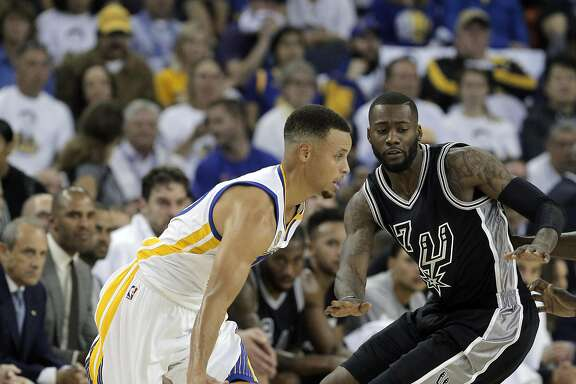 Stephen Curry (30) drives to the basket around Jonathon Simmons (17) in the first half as the Golden State Warriors played the San Antonio Spurs in their season opener at Oracle Arena in Oakland, Calif., on Tuesday, October 25, 2016.