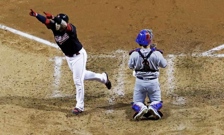 Cleveland Indians' Roberto Perez (55) celebrates his home run in front of Chicago Cubs catcher David Ross during the fourth inning of Game 1 of the Major League Baseball World Series Tuesday, Oct. 25, 2016, in Cleveland. (AP Photo/David J. Phillip)