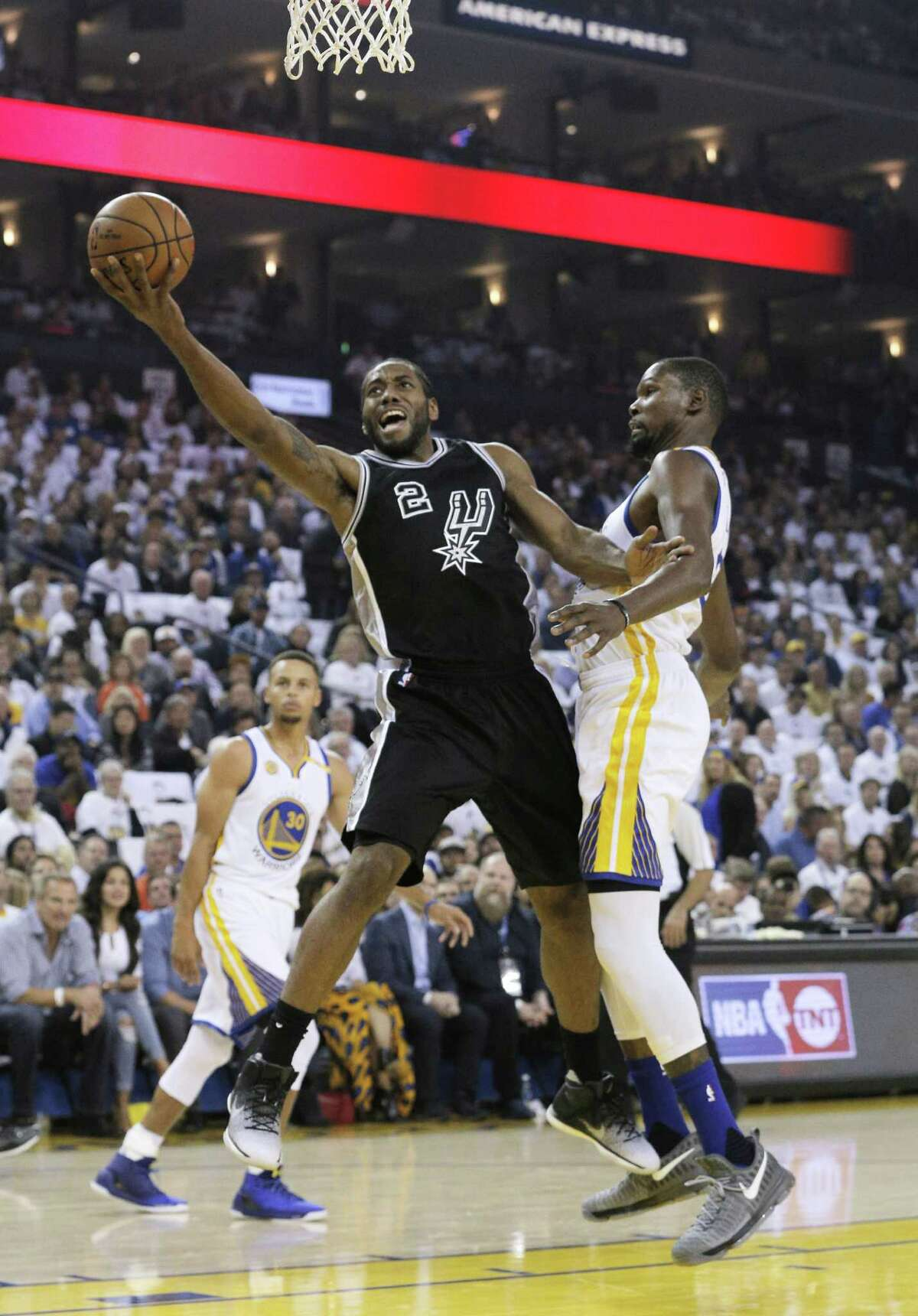 Kawhi Leonard (2) drives to the basket past Kevind Durant (35) in the first half as the Golden State Warriors played the San Antonio Spurs in their season opener at Oracle Arena in Oakland, Calif., on Tuesday, October 25, 2016.