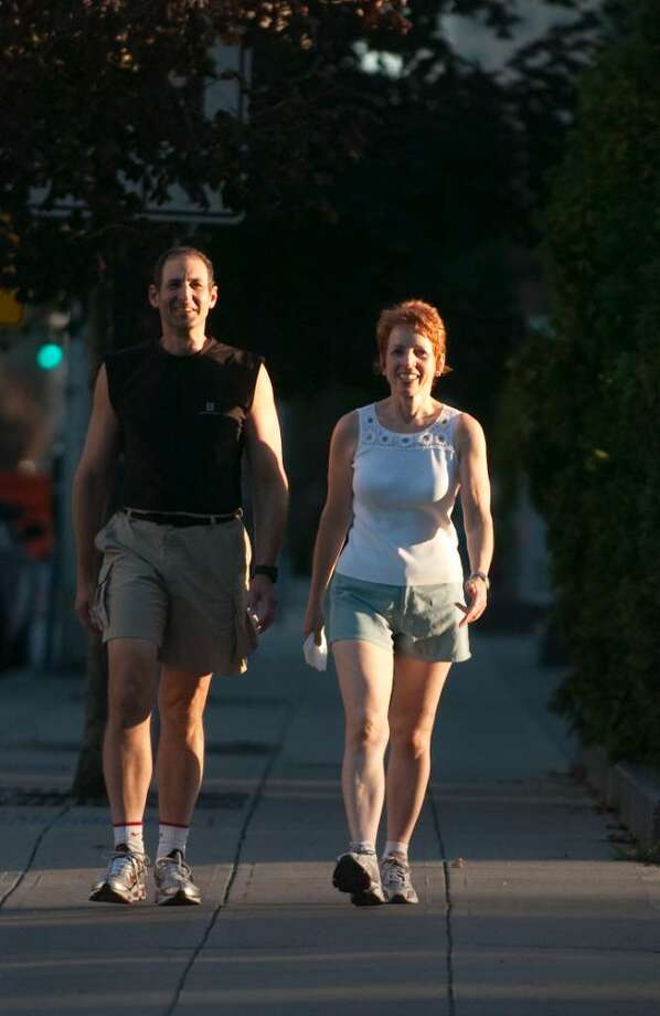 Myles Cohen, 58, and his wife Mary, 55, walk their usual route in downtown Stamford on Tuesday, September 1, 2009. Photo: Chris Preovolos / Stamford Advocate