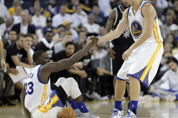 Klay Thompson (11) helps Draymond Green (23) after he was knocked down in the second half as the Golden State Warriors played the San Antonio Spurs in their season opener at Oracle Arena in Oakland, Calif., on Tuesday, October 25, 2016.