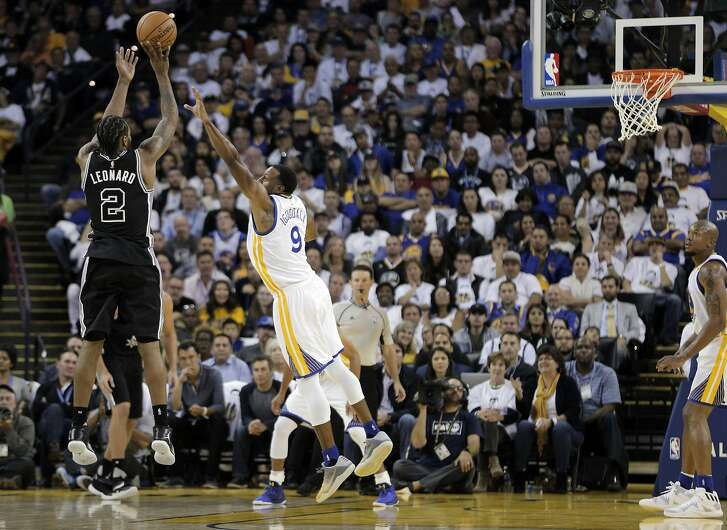 Kawhi Leonard (9) shoots over Andre Iguodala (9) in the second half as the Golden State Warriors played the San Antonio Spurs in their season opener at Oracle Arena in Oakland, Calif., on Tuesday, October 25, 2016.