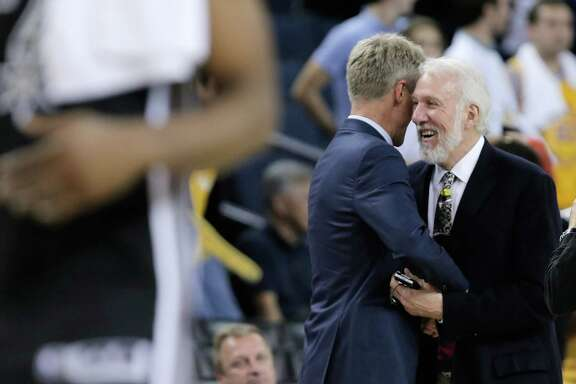 Steve Kerr, left, hugs Gregg Popovich, right after game as the Golden State Warriors played the San Antonio Spurs in their season opener at Oracle Arena in Oakland, Calif., on Tuesday, October 25, 2016.