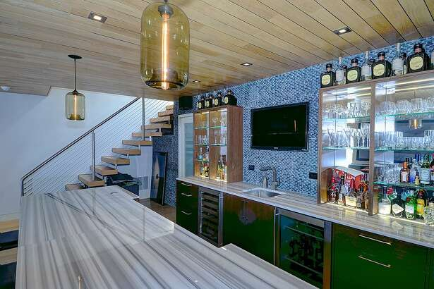 The full-service bar on the lower level has a long counter that accommodates four stools and glass-front cabinets with interior lighting and glass shelving.