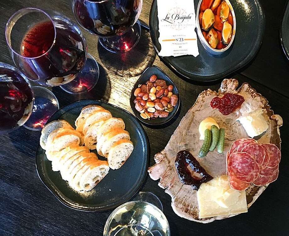 A flight of red wines, a glass of white Burgundy and cheese and charcuterie from High Street Wine Co. at The Pearl. The board includes La Tur soft and Sapore firm cheeses, rosette de Lyon salumi, cornichons, mustard, chile jam and fruit preserves. Photo: Mike Sutter /San Antonio Express-News