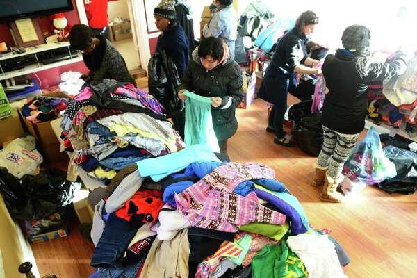 Residents look through donated clothes at the Bridgeport Rescue Mission on Fairfield Avenue in Bridgeport, Conn. on Wednesday Jan. 6, 2016. The mission needs 3,000 turkey and 15,000 coats to help people in need during Thanksgiving and the coming winter.