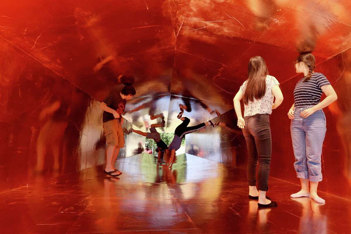 """Jaci Elliott, left, and Kathy Matlage try to lift themselves up-side-down in the tunnel of Havel Ruck Projects' """"Sharp,"""" a midcentury modern house in Sharpstown that's been turned into an art installation."""