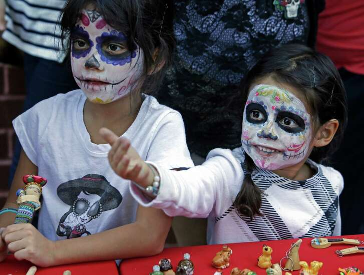 Nadia DeLavega, left, and her sister, Adina DeLavega, look at items for sale during a Dia De Los Muertos festival held last year.