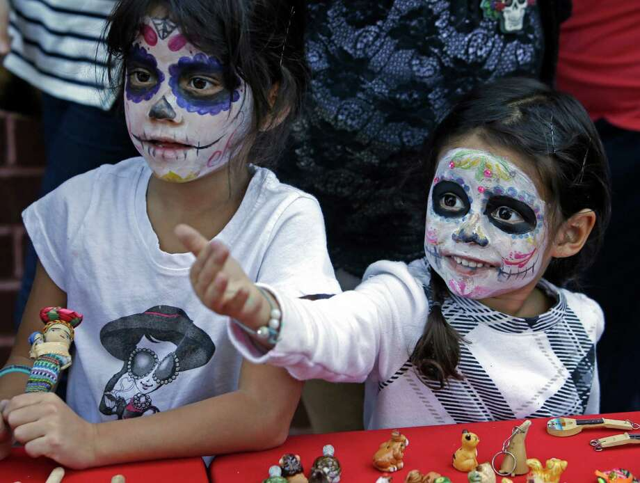 Nadia DeLavega, left, and her sister, Adina DeLavega, look at items for sale during a Día De Los Muertos festival last year.  Photo: Melissa Phillip, Staff / © 2015 Houston Chronicle