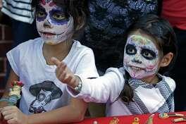 Nadia DeLavega, left, and her sister, Adina DeLavega, look at items for sale during a Dia De Los Muertos festival held last year.