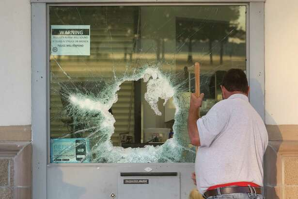 Mitch Kohler, who manages a glass company, cleans broken glass before putting a pre-cut piece of wood over a broken drive-through window at a Walgreens in the 12700 block of Bammel North Houston Road, Wed. Oct. 26, 2016, in Houston.