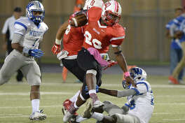 Robert Atlee (20) of Bellaire leaps past a Westbury defender on a kickoff return at the start of the third quarter of a high school football game between the Bellaire Cardinals and the Westbury Huskies on Thursday October 20, 2016 at Butler Stadium, Houston, TX.