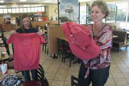 Deerwood Elementary counselor Holly Mays and Shadow Forest Elementary principal Lisa Lackey put on shirts from Willow Creek Elementary as they were the first place winners in the elementary school spirit competition at the Chick-fil-A Kingwood Tuesday, Oct. 25.