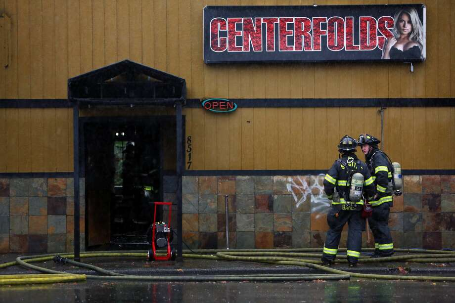 Firefighters stand by after a fire broke out at Centerfolds strip club at North 85th Street and 15th Street Northwest in Ballard, Wednesday morning around 8:15am. Photo: GENNA MARTIN/SEATTLEPI.COM