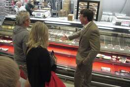 H-E-B Unit Director Tony Klaus explains a few of the new meats and dry aged beef that will be available at the new H-E-B Kingwood Market during a sneak preview tour Tuesday, Oct. 25.