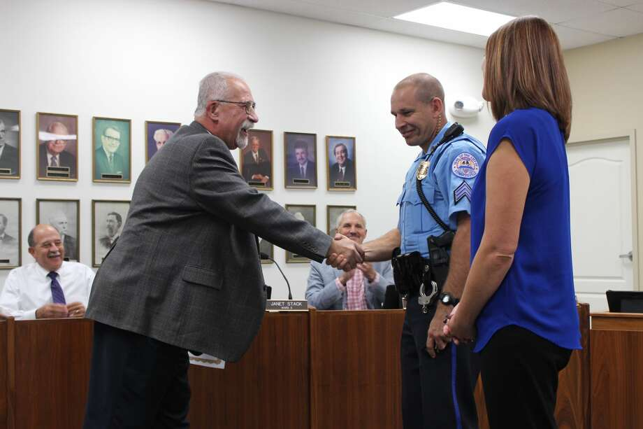 Justin Towell of the Edwardsville Police Department shakes hands with City Clerk Dennis McCracken after being sworn in as the new police sergeant for the city of Edwardsville.