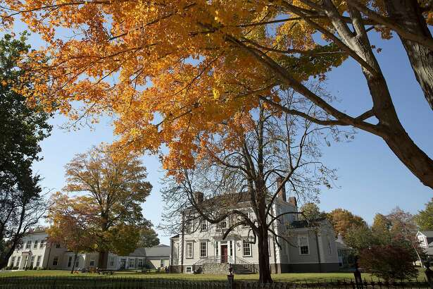 In this Tuesday, Oct. 18, 2016 photo, a tree changes color in front of historic buildings on the campus of Lyme Academy College of Fine Arts in Old Lyme, Conn. A plan to speed up Amtrak's high-speed rail corridor from Boston to Washington, D.C., is welcomed by business commuters but finding its strongest opposition in some shoreline towns in Connecticut. (AP Photo/Michael Dwyer)