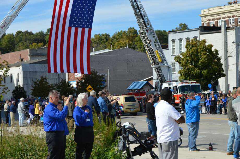 The Hearse travels under an American Flag suspended by two firetrucks in downtown Alton. Photo: By JOHN SOMMERHOF
