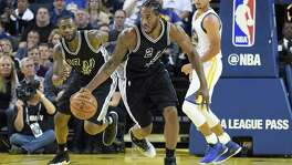 Kawhi Leonard of the Spurs dribbles up court against the Golden State Warriors during the third quarter at Oracle Arena on Oct. 25, 2016 in Oakland, Calif.