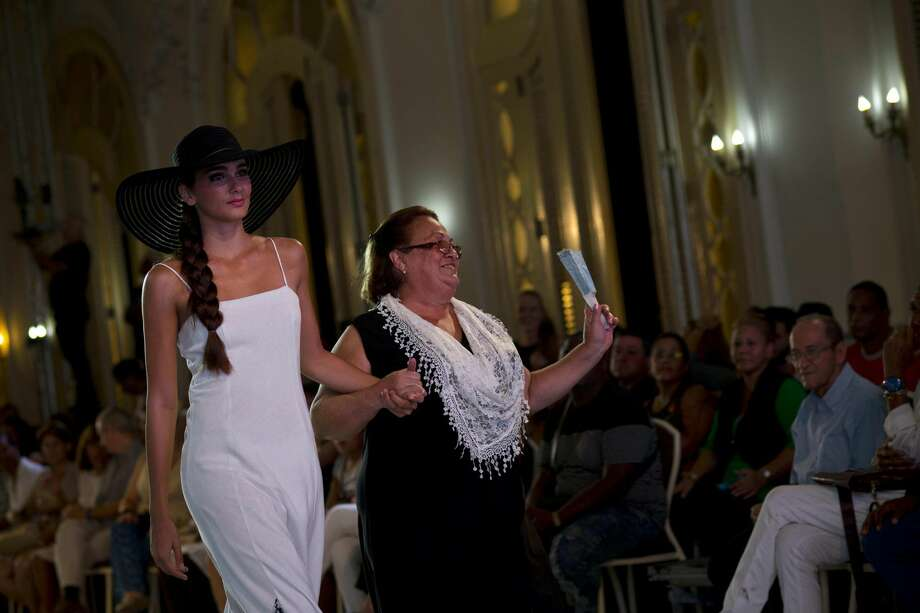 In this Oct. 14, 2016 photo, Cuban fashion designer Analu, center, walks down the catwalk with a model during Havana Fashion Week at the Alicia Alonso Grand Theater in Havana, Cuba. Analu is one of Cuba's hundreds of private designers are turning out gauzy wedding dresses, brilliantly decorated bathing suits, linen pants and even uniforms for state businesses. (AP Photo/Ramon Espinosa) Photo: Ramon Espinosa/Associated Press