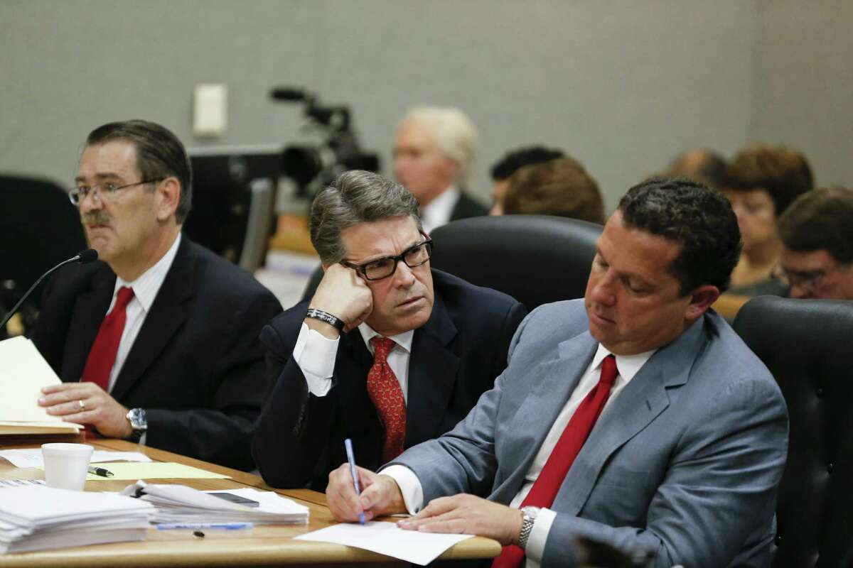 Texas Governor Rick Perry appears in Travis County Court on Thursday to answer charges in an indictment regarding his veto of funding for the Travis County Public Integrity Unit. He peers at defense lawyer Tony Buzbee as a second attorney David Botsford is on the left.