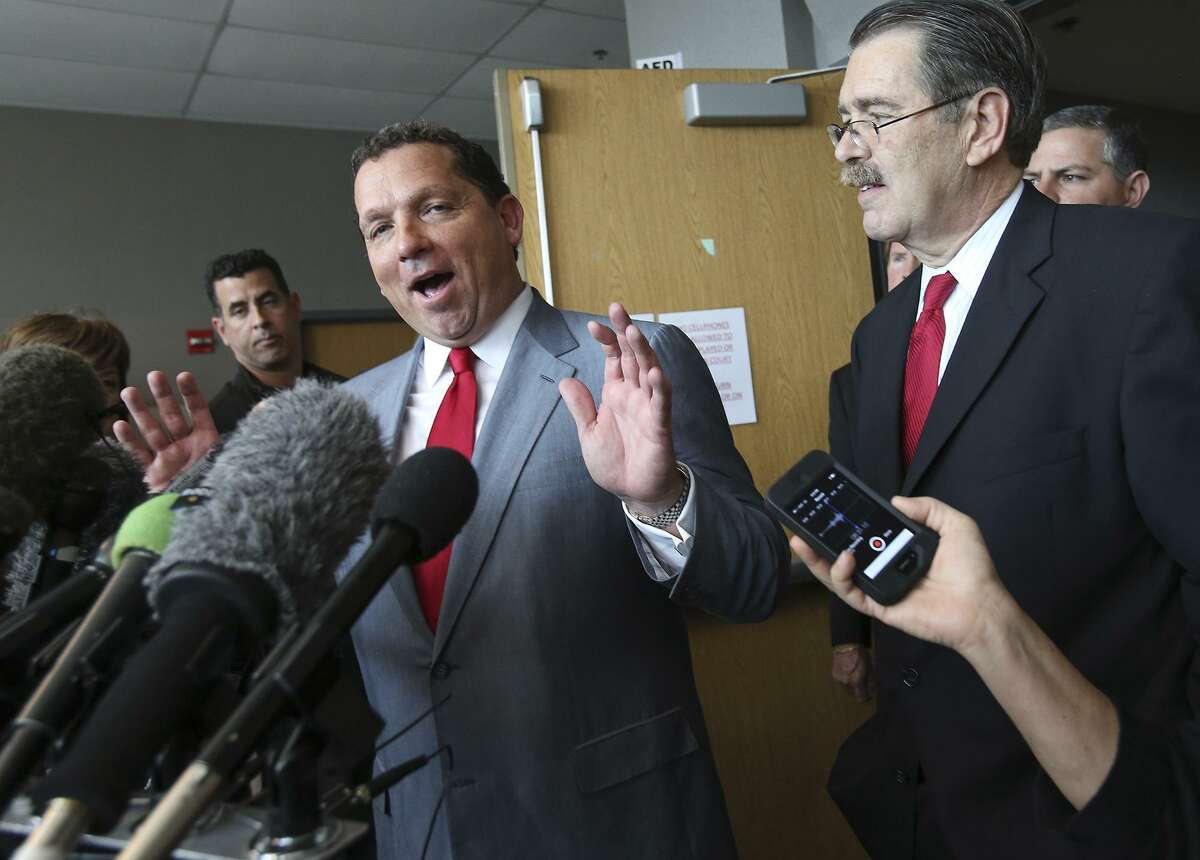 Defense lawyer Tony Buzbee answers questions with attorney David Botsford following Gov. Rick Perry's remarks after appearing at a hearing in the 390th District Court at the Travis County Courthouse on November 6, 2014.