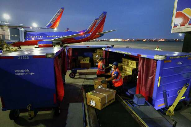Tamika Jackson, right, and Audrey Freeman help load live blue crabs onto a Southwest Airlines flight to Baltimore at Hobby Airport, Thursday, May 12, 2016, in Houston. The seafood distributor T & Y Seafood uses Southwest Airlines to ship live crabs across the country.  ( Jon Shapley / Houston Chronicle )