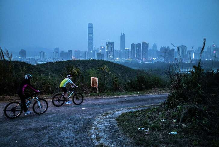 """HONG KONG - APRIL 01:  People cycles at Kwu Tong with backdrop of Shenzhen on April 1, 2016 in Hong Kong. Despite recent protests seen from Hong Kong's opposition lawmakers on the construction of a high-speed rail linking the city to Shenzhen and Guangzhou, Hong Kong's future has been increasingly dependent on China's megacities across the border. Also known for being the global hub for China, Hong Kong's economic role in the region faces further challenges as its neighbouring mainland cities continue to grow. Last year the disappearance of a Hong Kong bookseller, followed by his reappearance on the mainland, has caused concerns that security officers from mainland China had taken him across the 37km-long border, which would have violated the """"one country, two systems"""" arrangement since the return of Hong Kong on 1997.  (Photo by Lam Yik Fei/Getty Images)"""