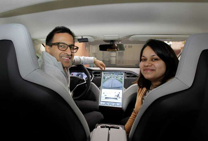 Rakesh Agrawal and his wife, Shonali, in the family's Tesla Model S electric car. Their daughter grieved for the old car - then Tesla's technology won her over.