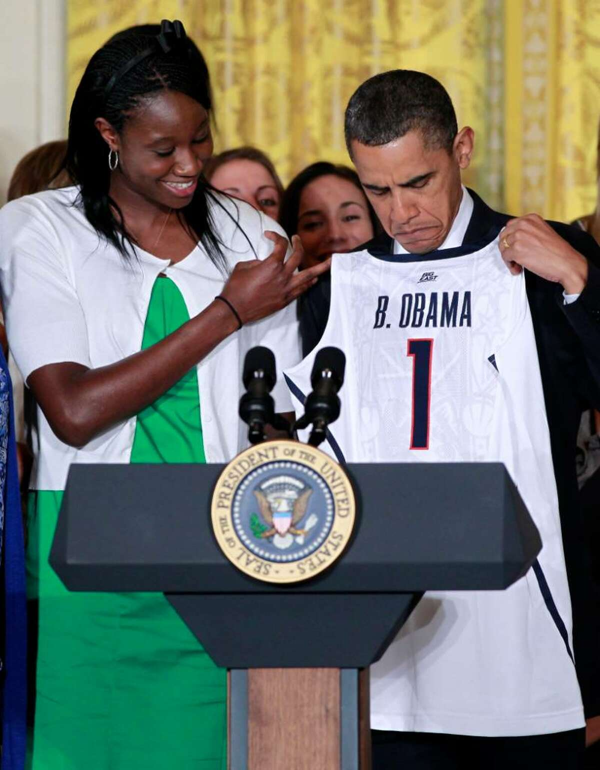 President Barack Obama is presented with a personalized team jersey by Tina Charles as he honored the 2010 NCAA champion University of Connecticut women's basketball team in the East Room of the White House in Washington, Monday, May 17, 2010. (AP Photo/Charles Dharapak)