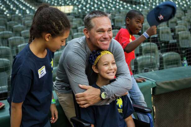 Former Houston Astros second baseman Craig Biggio embraces Eden Green as he poses for a photo with Eden, her sister, Mya, and Trey Thomas during the annual Sunshine Kids party at Minute Maid Park Wednesday, Oct. 26, 2016, in Houston. More than 100 young cancer patients and their siblings participated in baseball activities on the field and then were treated to lunch in the Diamond Club with volunteers from the Astros and KBR. Astros Hall of Famer Craig Biggio and his wife, Patty, have worked closely with  the Sunshine Kids, a non-profit organization dedicated to children with cancer and their families, for more than 20 years.