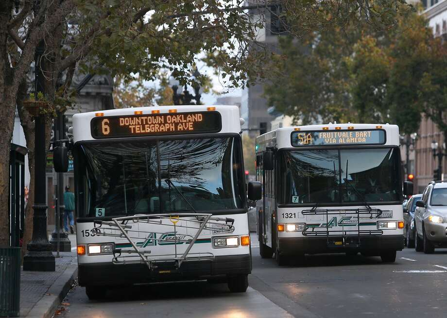 AC Transit buses drive on Broadway near City Hall in Oakland, Calif. on Wednesday, Oct. 26, 2016. Measure C1 on the Alameda County ballot is one of several tax proposals that Bay Area voters will consider to support public transportation. Photo: Paul Chinn / The Chronicle