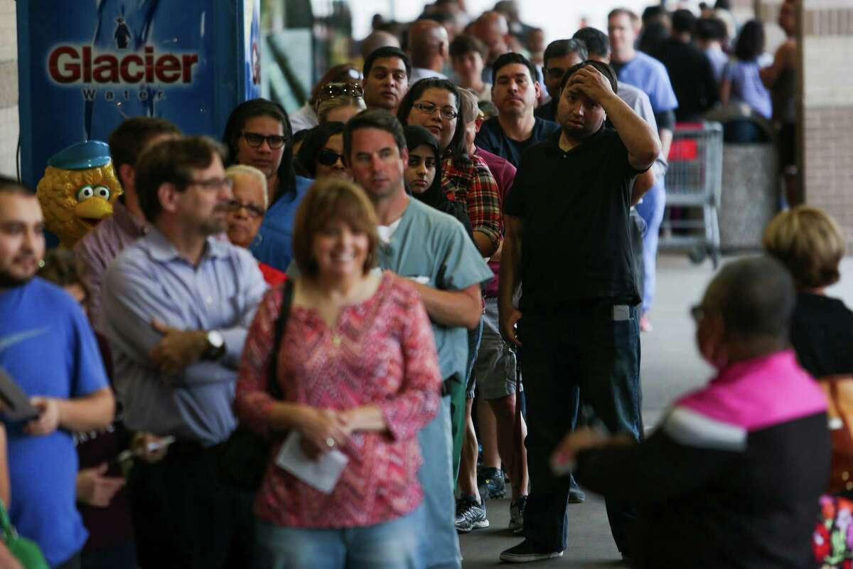 Hundreds of people wait in line to cast their ballot at the Fiesta Mart, 8130 Kirby Drive in southwest Houston, during the first day of early voting.