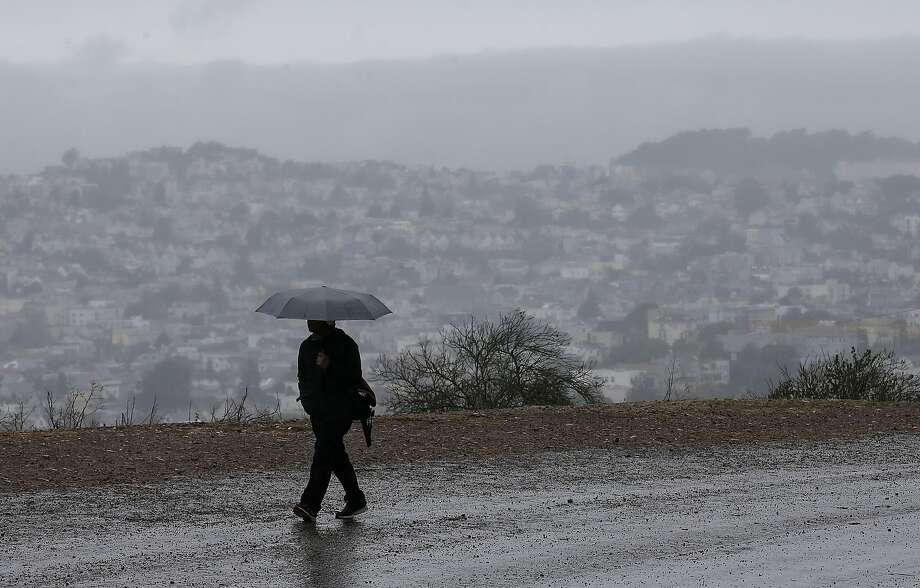 A man carries an umbrella while walking along a road on Bernal Heights Hill in San Francisco, Friday, Oct. 14, 2016. Intermittent showers, and some heavy downpours, are forecast to hit the Bay Area Thursday and last through Monday morning. Photo: Jeff Chiu, Associated Press