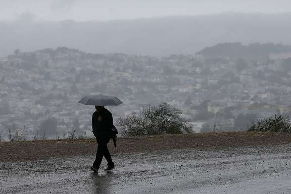 A man carries an umbrella while walking along a road on Bernal Heights Hill in San Francisco, Friday, Oct. 14, 2016. Rain, wind and coastal flooding is expected to affect the San Francisco Bay Area through part of Saturday. (AP Photo/Jeff Chiu)