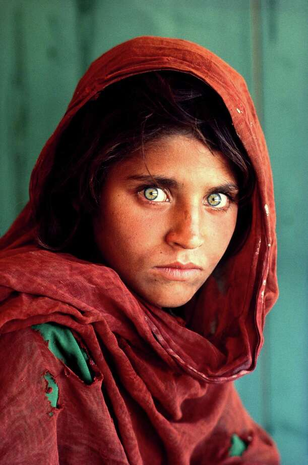 At left, Sharbat Gula in her iconic 1984 photo. At right, Gula is shown on Wednesday after her arrest in Pakistan on ID fraud charges. Photo: Steve McCurry / Houston Chronicle