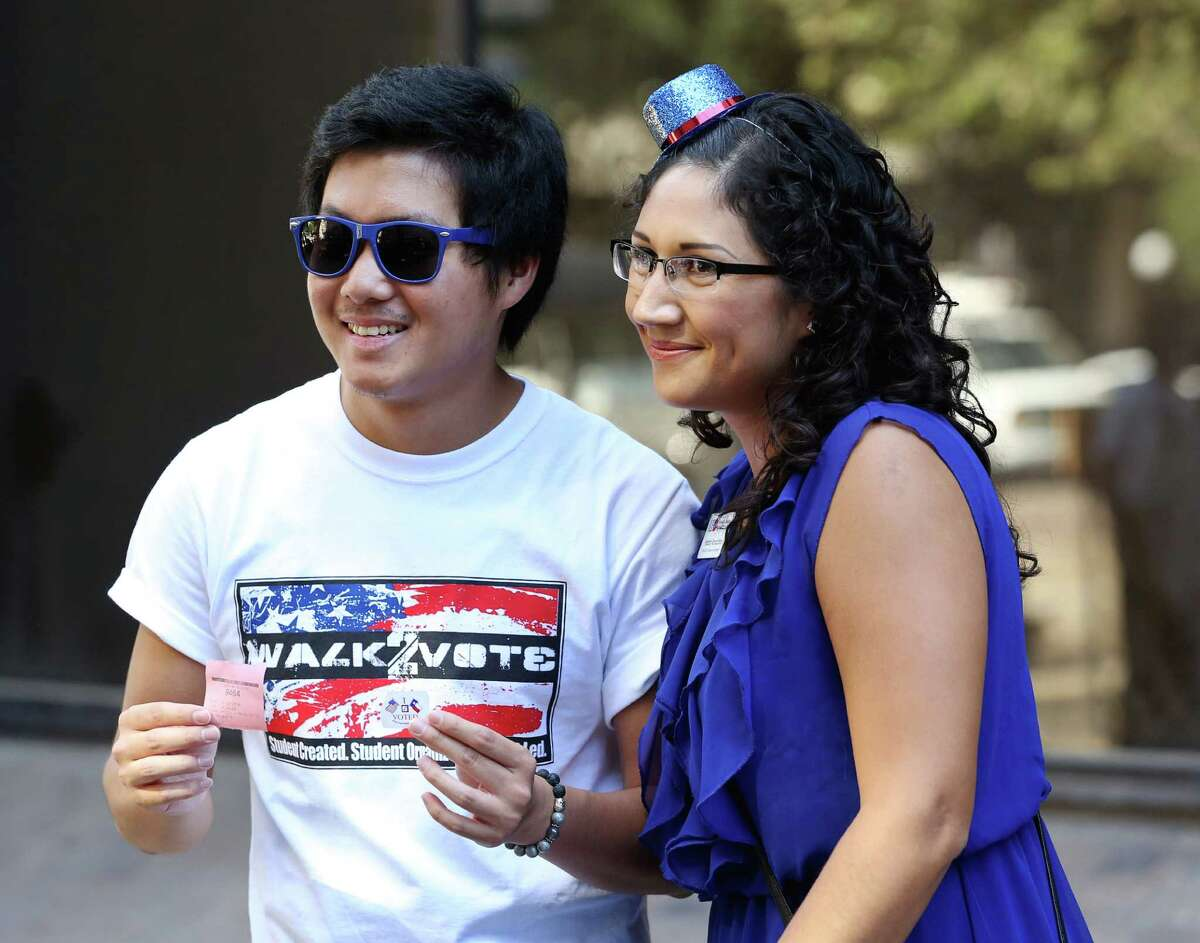 University of Houston-Downtown student Nghia Nguyen takes a photo with Hatziri Rancano after casting his vote at Harris County Tax Office. They helped lead a student voter event.