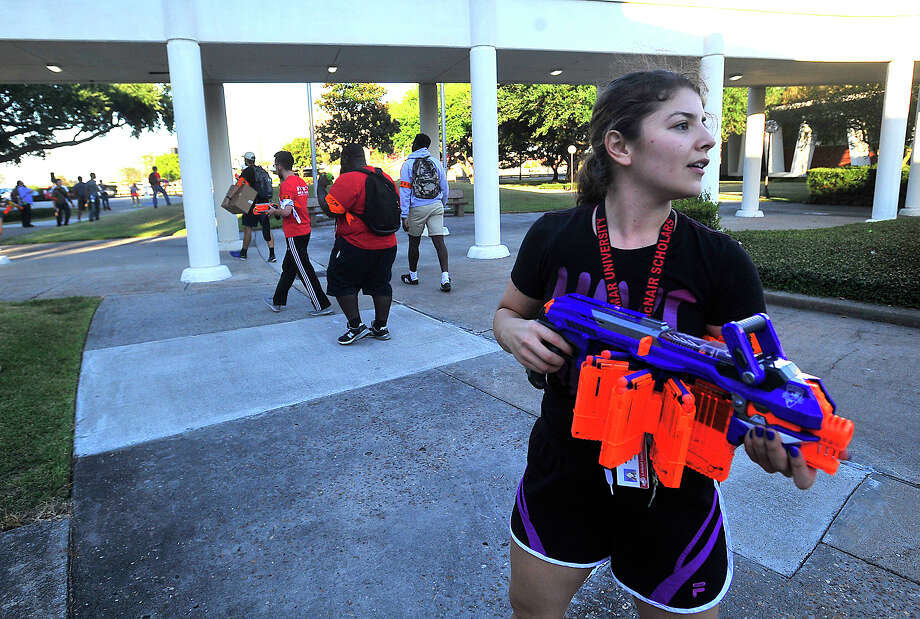 Miroslava Zendejas keeps watch for zombies approaching from the rear as she and fellow humans, armed with Nerf weapons, search for components to complete their mission during a game of Humans vs. Zombies tag on campus at Lamar University Wednesday. Roughly 100 students signed up to participate in the homecoming week activity, which is taking place every day on campus. Participants can play throughout the day and meet up in early evening to complete various missions that send them in search of objects hidden throughout campus while trying to avoid being tagged and turned into a zombie. Photo taken Wednesday, October 26, 2016 Kim Brent/The Enterprise Photo: Kim Brent / Beaumont Enterprise