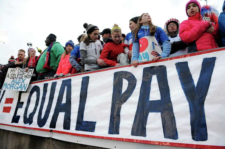 FILE - In this April 6, 2016, file photo, fans stand behind a large sign for equal pay for the women's soccer team during an international friendly soccer match between the United States and Colombia at Pratt & Whitney Stadium at Rentschler Field in East Hartford, Conn. The World Economic Forum's annual Global Gender Gap Report released on Oct. 25, 2016, found that the global gender pay gap will not be closed for another 170 years if current trends continue. (AP Photo/Jessica Hill, File) ORG XMIT: PAPM103 Photo: Jessica Hill / FR125654 AP