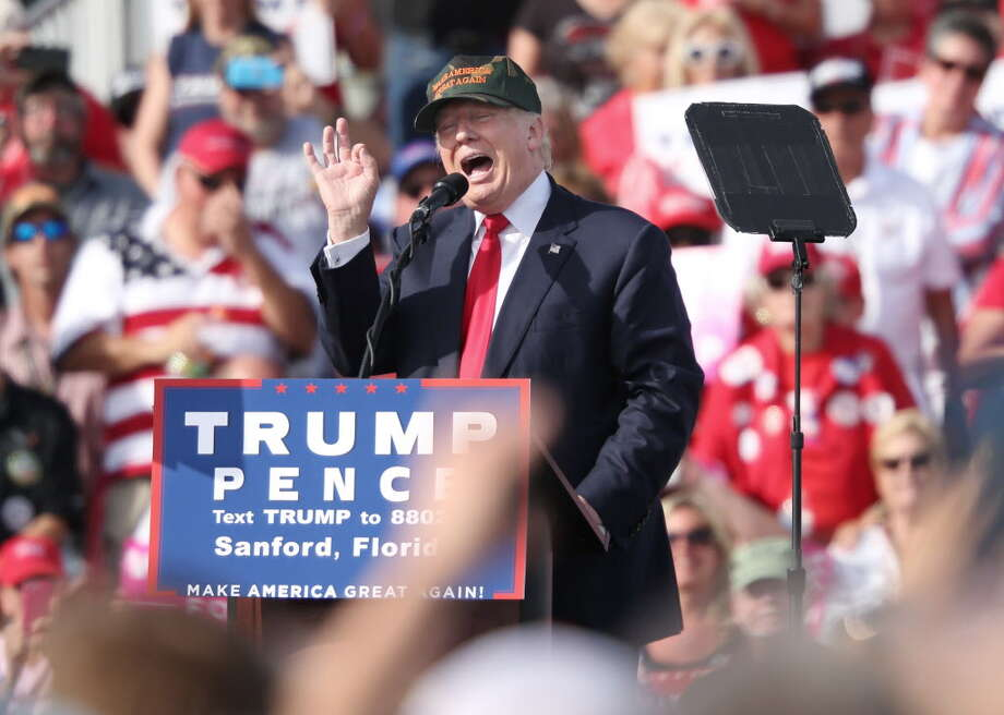 TOPSHOT - Republican presidential nominee Donald Trump addresses supporters at a rally on the tarmac of the Orlando-Sanford International Airport in Sanford, Florida on October 25, 2016. / AFP PHOTO / Gregg NewtonGREGG NEWTON/AFP/Getty Images ORG XMIT: Republica Photo: GREGG NEWTON / AFP or Licensors