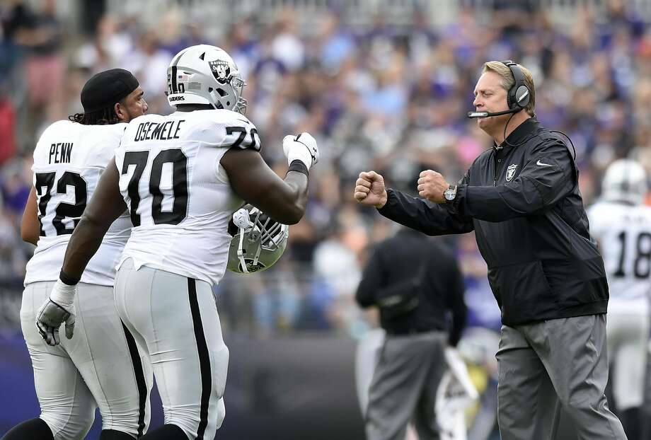 Oakland Raiders head coach Jack Del Rio, right, fist-bumps tackle Donald Penn (72) and offensive guard Kelechi Osemele after a Raiders touchdown in the first half of an NFL football game against the Baltimore Ravens, Sunday, Oct. 2, 2016, in Baltimore. (AP Photo/Gail Burton) Photo: Gail Burton, Associated Press